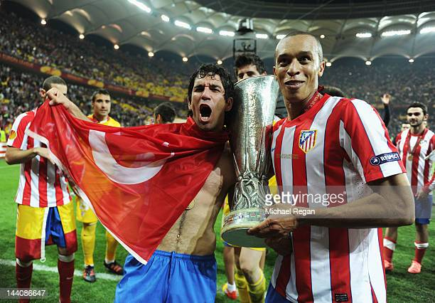 Arda Turan and Miranda of Atletico Madrid celebrate with the trophy at the end of the UEFA Europa League Final between Atletico Madrid and Athletic...