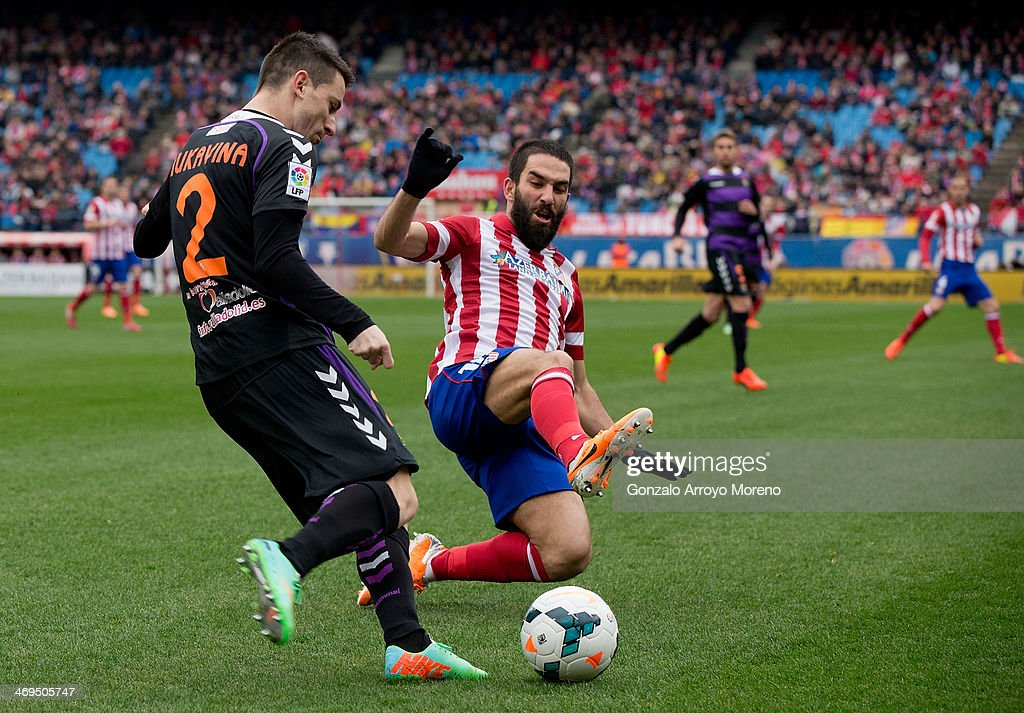 Arda Turan (R) of Atletico de Madrid competes for the ball with Antonio Rukavina (L) of Real Valladolid CF during the La Liga match between Club Atletico de Madrid and Real Valladolid CF at Vicente Calderon Stadium on February 15, 2014 in Madrid, Spain.
