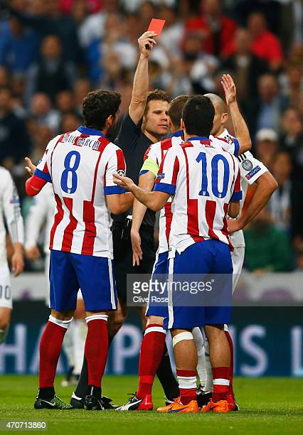 Arda Turan of Atletico Madrid is sent off by referee Felix Brych during the UEFA Champions League quarterfinal second leg match between Real Madrid...