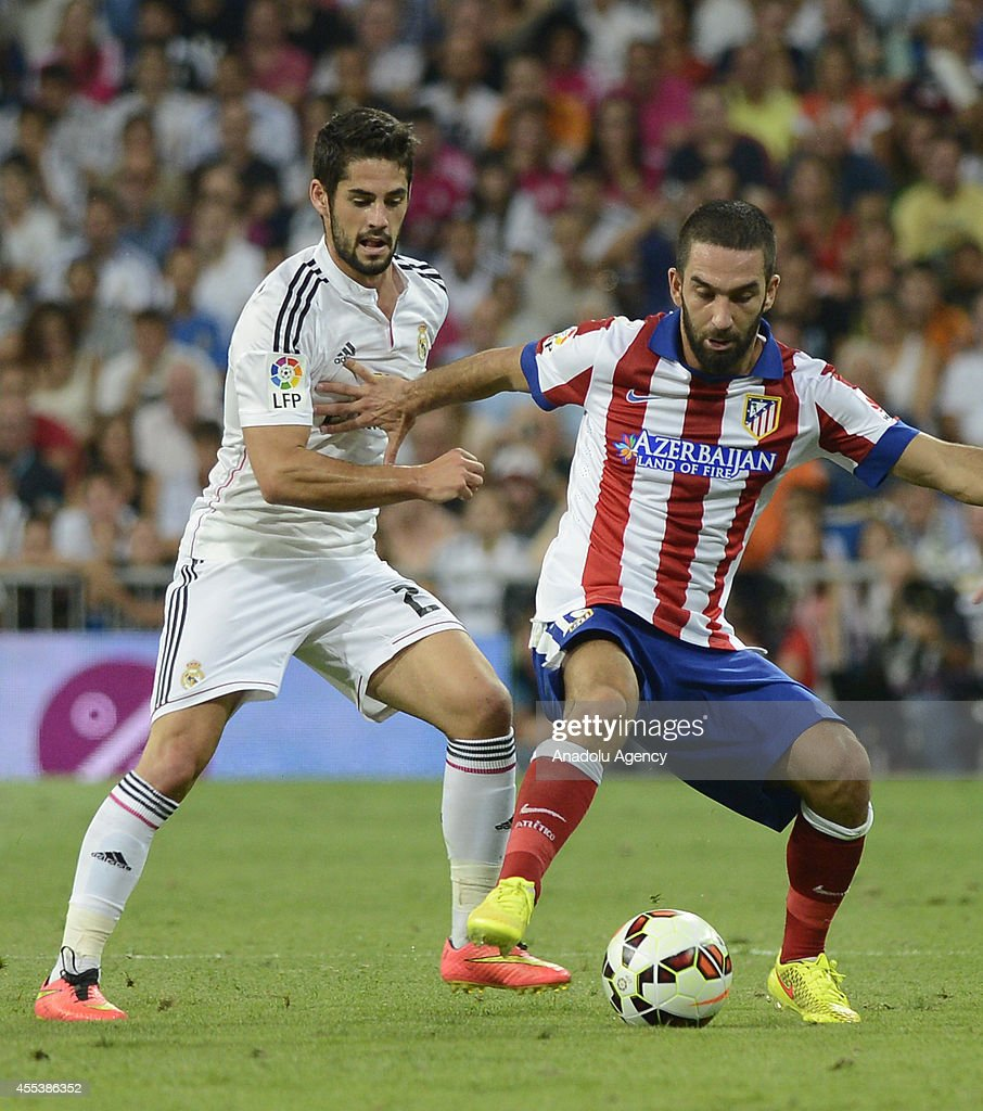 Arda Turan (R) of Atletico Madrid vies for the ball with Isco (L) of Real Madrid during the Spanish La Liga soccer match between Real Madrid and Atletico Madrid at the Santiago Bernabeu stadium in Madrid, Spain on September 13, 2014.