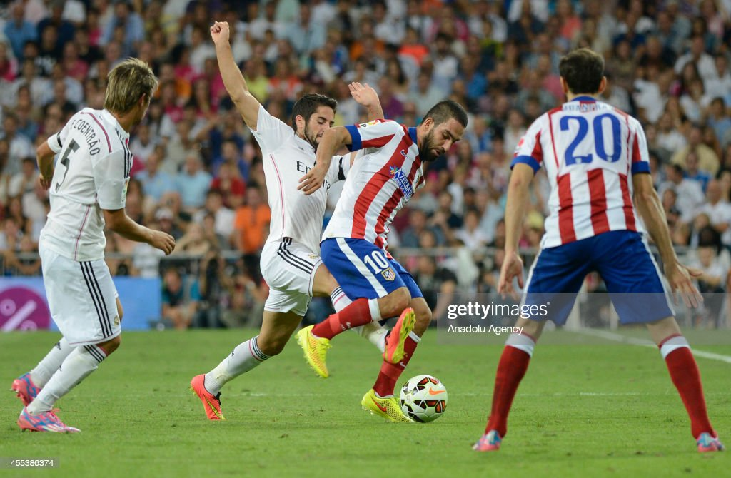 Arda Turan (10) of Atletico Madrid vies for the ball with Isco (2nd L) of Real Madrid during the Spanish La Liga soccer match between Real Madrid and Atletico Madrid at the Santiago Bernabeu stadium in Madrid, Spain on September 13, 2014.
