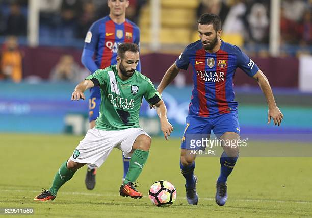 Arda Turan of Barcelona in action against Gianns Fetfatzidis of Al-Ahli Saudi FC during the Qatar Airways Cup match between FC Barcelona and Al-Ahli...