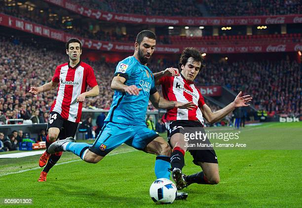 Arda Turan of FC Barcelola duels for the ball with Inigo Lekue of Athletic Club during the Copa del Rey Quarter Final First Leg match between...