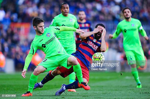 Arda Turan of FC Barcelona competes for the ball with Alvaro Medran of Getafe CF during the La Liga match between FC Barcelona and Getafe CF at Camp...