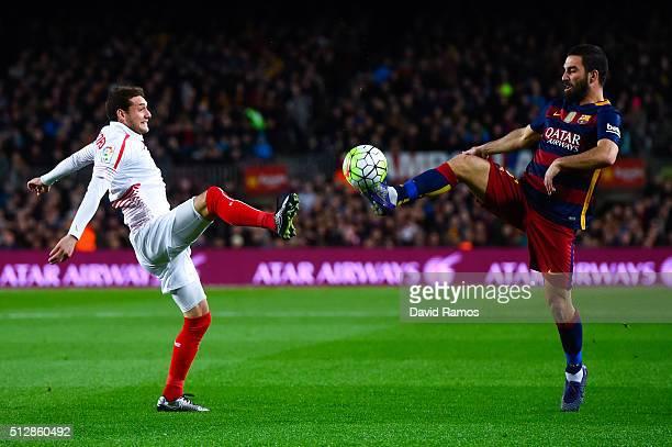 Arda Turan of FC Barcelona competes for the ball with Sebastian Cristoforo of Sevilla FC during the La Liga match between FC Barcelona and Sevilla FC...