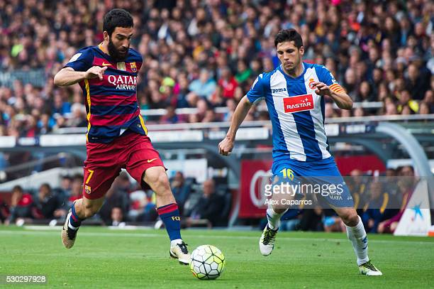 Arda Turan of FC Barcelona controls the ball next to Javi Lopez of RCD Espanyol during the La Liga match between FC Barcelona and RCD Espanyol at...