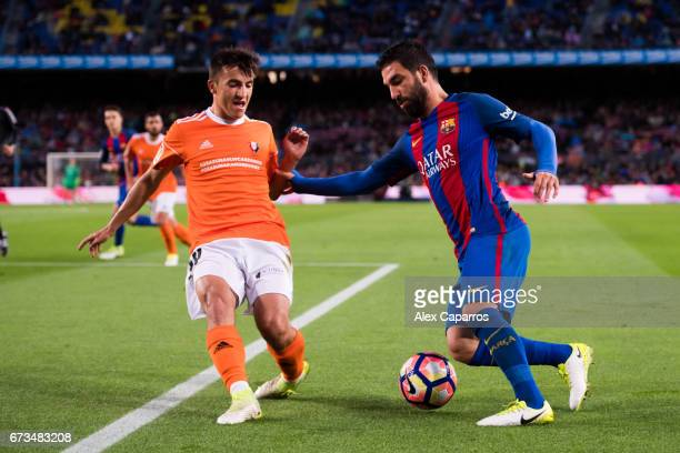 Arda Turan of FC Barcelona dribbles Aitor Bunuel of CA Osasuna during the La Liga match between FC Barcelona and CA Osasuna at Camp Nou stadium on...