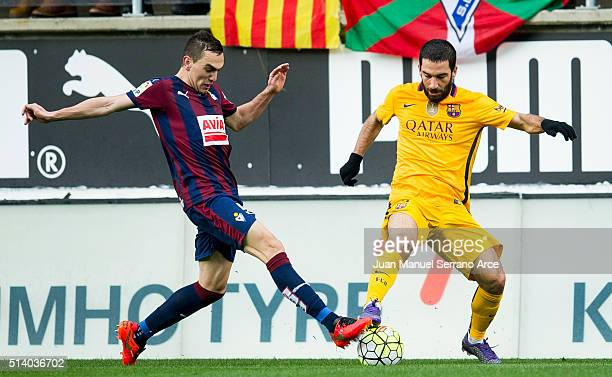 Arda Turan of FC Barcelona duels for the ball with Gonzalo Escalante of SD Eibar during the La Liga match between SD Eibar and FC Barcelona at Ipurua...