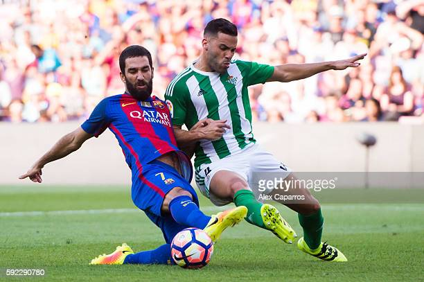 Arda Turan of FC Barcelona fights for the ball with Bruno Gonzalez of Real Betis Balompie during the La Liga match between FC Barcelona and Real...