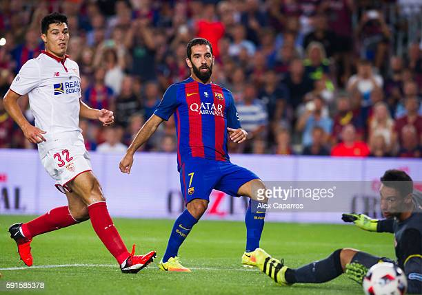 Arda Turan of FC Barcelona shoots the ball past goalkeeper Sergio Rico and next to Diego Gonzalez of Sevilla FC and scores the opening goal during...