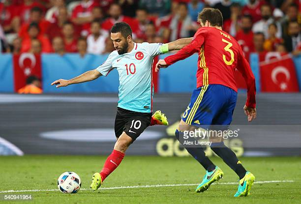 Arda Turan of Turkey curls the ball past Gerard Pique of Spain during the UEFA EURO 2016 Group D match between Spain and Turkey at Allianz Riviera...