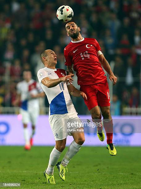 Arda Turan of Turkey jumps for a header over Netherlands Jordy Clasie during FIFA 2014 World Cup Qualifier match at the Sukru Saracoglu Stadium on...