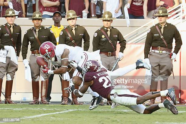 ArDarius Stewart of the Alabama Crimson Tide dives for the football in front of Brandon Williams of the Texas AM Aggies as a group of cadets looks on...