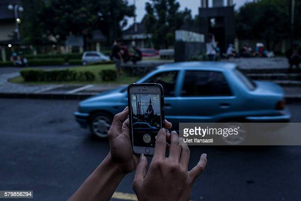 Ardi plays Pokemon Go game on his smartphone in the street on July 23 2016 in Yogyakarta Indonesia Pokemon Go which uses Google Maps and a smartphone...