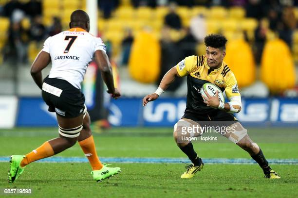 Ardie Savea of the Hurricanes attempts to evade the defnce of Oupa Mohoje of the Cheetahs during the round 13 Super Rugby match between the...