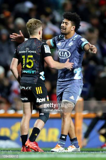 Ardie Savea of the Hurricanes hugs Damian McKenzie of the Chiefs after winning the round 4 Super Rugby Aotearoa match between the Chiefs and the...