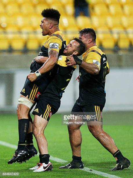 Ardie Savea of the Hurricanes is congratulated on his matchwinning try by teammate Jamison GibsonPark and Chris Eves during the round 14 Super Rugby...