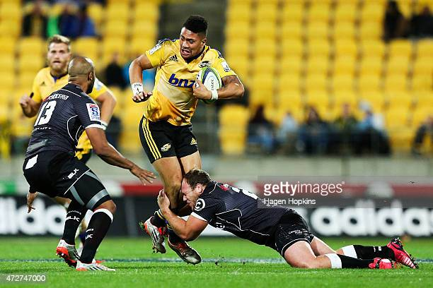 Ardie Savea of the Hurricanes is tackled by Kyle Cooper and JP Pietersen of the Sharks during the round 13 Super Rugby match between the Hurricanes...