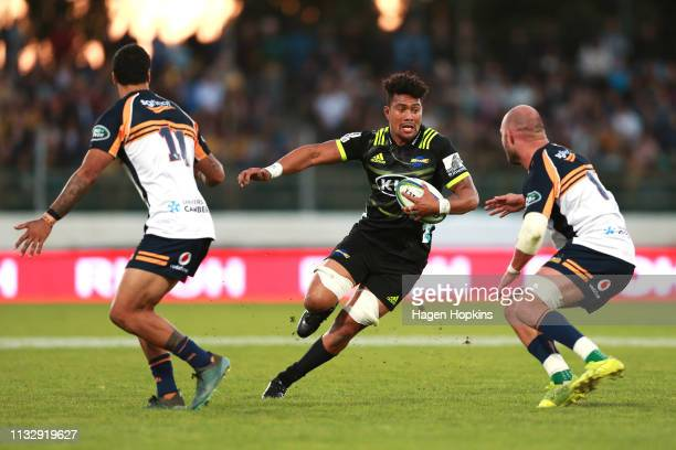 Ardie Savea of the Hurricanes runs at Lachlan McCaffrey and Chance Peni of the Brumbies during the round three Super Rugby match between the...