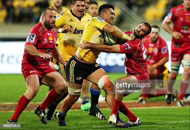 Ardie Savea of the Hurricanes runs over the defence of Nick Frisby of the Reds on his way to scoring a try during the round 11 Super Rugby match...