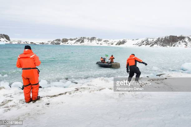 Arduous ship boarding operation with divers in zodiacs under ice on November 04 2019 in King George Island Antarctica
