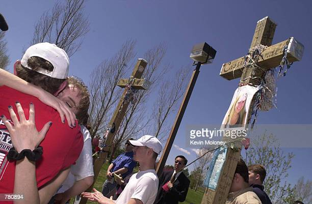 Area high school student Kristina Metter gets a hug after helping set up a row of thirteen crosses in Robert F Clement Park April 20 2000 in...