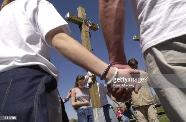 Area high school student Kristina Metter weeps during a prayer at a row of thirteen crosses in Robert F Clement Park in Littleton CO April 20 2000...