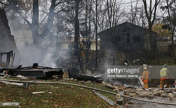 Area police and firefighters work at the scene after a passenger jet crashed into a home on Mogadore Road while on a short approach to AkronFulton...