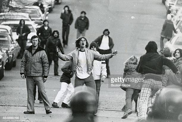 Area residents shout at police as the rioting crowd is moved down E 6th Street in South Boston on Dec 11 1974 A clash between police and a crowd of...