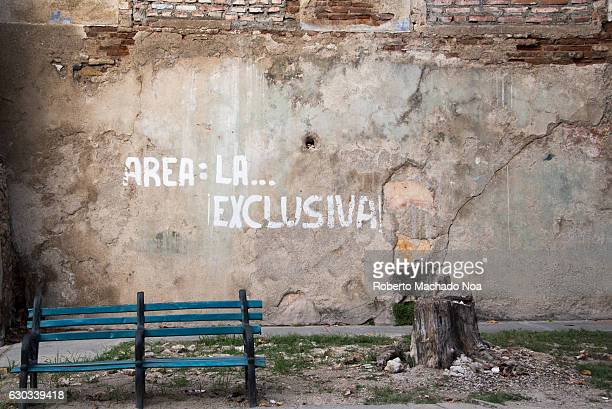Area 'The Exclusive' in a non tourist neighbourhood Cuban public scene with a teal colored seat bench tree stump and an ancient concrete wall in...