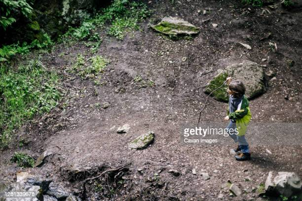 area view boy walking stick over mud by rocks and grass - petaluma stock pictures, royalty-free photos & images