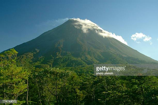 Arenal volcano Costa Rica. Cloud capped cone against blue sky.