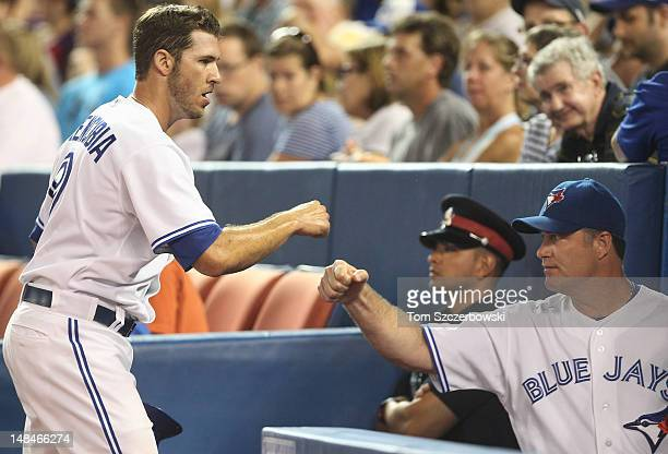 P Arencibia of the Toronto Blue Jays is congratulated by John Farrell after scoring in the 3rd inning on an RBI single by Colby Rasmus during MLB...