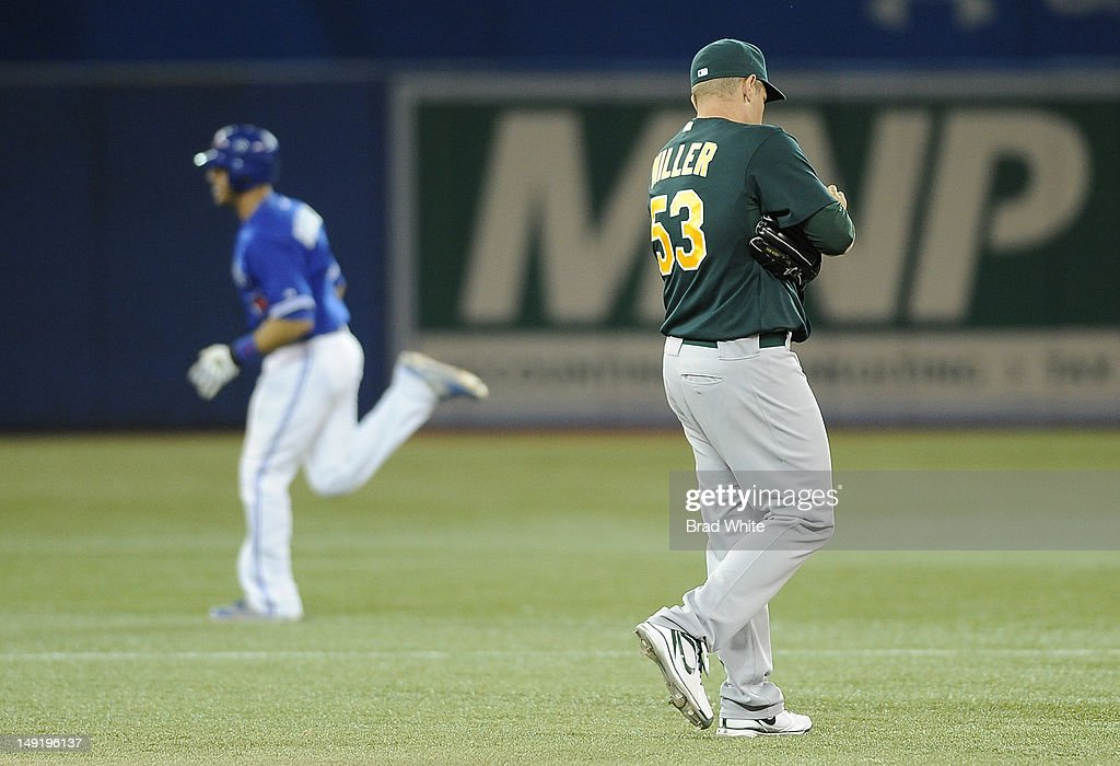 J.P. Arencibia #9 of the Toronto Blue Jays runs the bases as Jim Miller #53 of the Oakland Athletics looks on after giving up a home run during MLB game action July 24, 2012 at Rogers Centre in Toronto, Ontario, Canada.