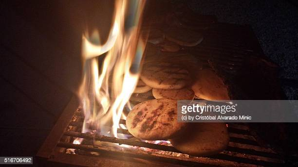 Arepas being cooked in the grill