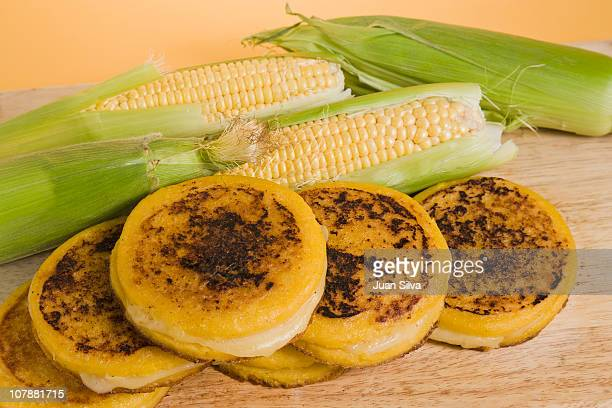Arepas with ear of corns on wooden board