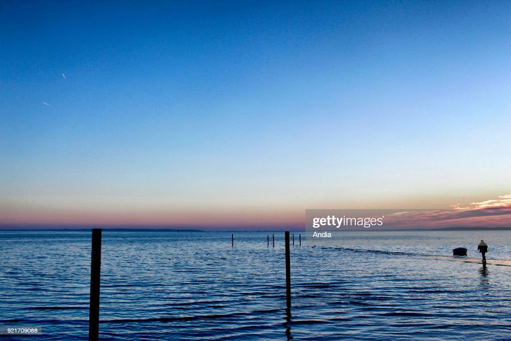 Ares jetty covered in water during a spring tide, in the Arcachon Bay, along the Atlantic coast: spring tide on . Man walking on the pier, alone, feet in the water.