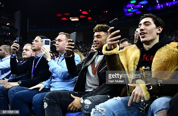 Aresnal team mates Hector Bellerin and Alex OxladeChamberlain use their phones during the NBA match between Indiana Pacers and Denver Nuggets at the...