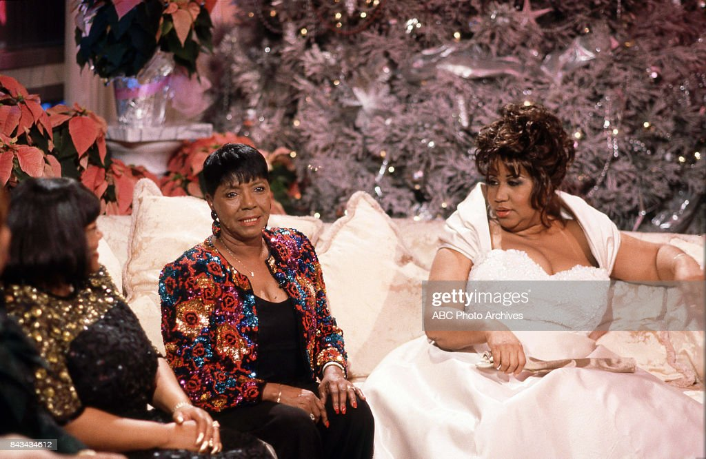 Aretha Franklin and her family sitting on couch on 'Christmas at Home with the Stars'.