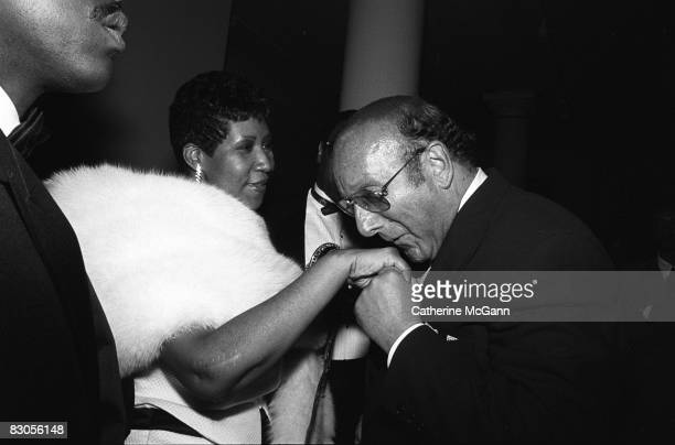 Aretha Franklin left extends her hand to be kissed by American record producer and music industry executive Clive Davis right at a party in July 1989...