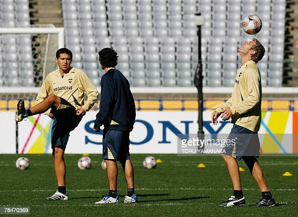 Argantine football club Boca Juniors forward Martin Palermo lifts a ball beside midfielder Juan Riquelme and another teammate during the practice...