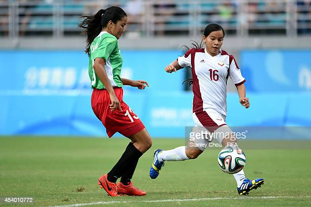 Argelis Campos of Venezuela competes with Akemi Yokoyama of Mexico during the 2014 FIFA Girls Summer Youth Olympic Football Tournament Semi Final...