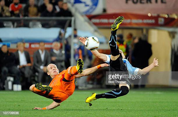 Argen Robben of the Netherlands challenged by Martin Caceres of Uruguay during the 2010 FIFA World Cup South Africa Semi Final match between Uruguay...