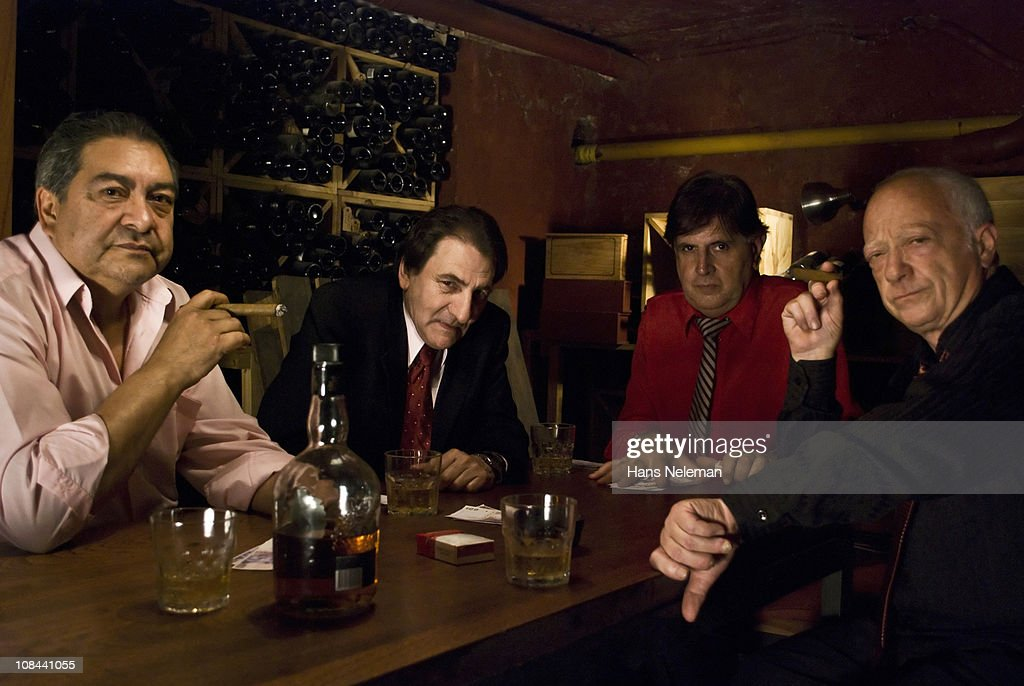 Argentina, Buenos Aires, Gangsters playing cards and smoking cigars : Stock Photo