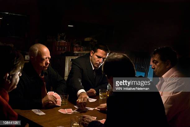 Argentina, Buenos Aires, Gangsters playing cards sitting by table at night