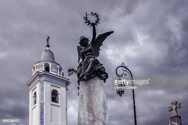 Argentina, Buenos Aires, Recoleta Cemetery, Statue and bell tower of Our Lady Del Pilar Church