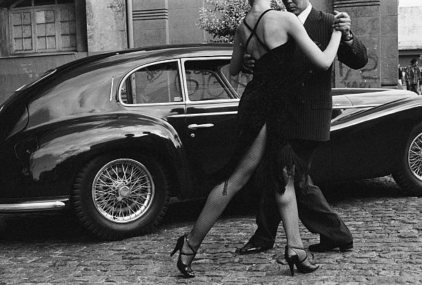 Argentina, couple dancing tango by car in street (B&W)