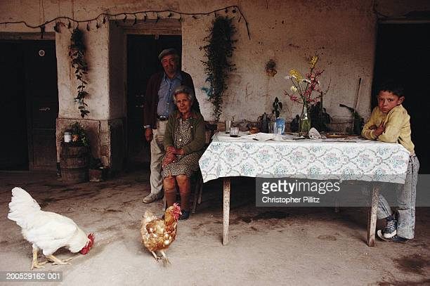 Argentina, family around table outside house, chickens in foreground