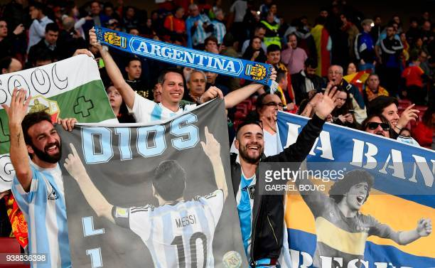 Argentina fans cheer with pictures of Argentina's forward Lionel Messi and Argentinian football legend Diego Maradona ahead of a friendly football...