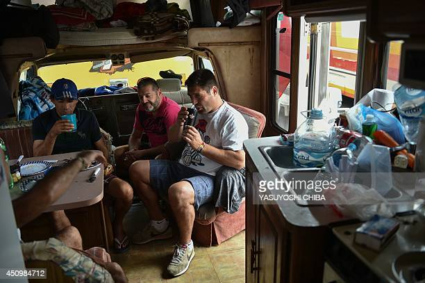 Argentina fans have breakfast inside a car before the group match between Argentina and Iran as they reside at a new camping site next to Sambadromo...